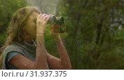 Купить «Woman observing the forest using binoculars», видеоролик № 31937375, снято 5 апреля 2019 г. (c) Wavebreak Media / Фотобанк Лори