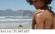 Купить «Woman applying sunscreen on shoulders at beach in the sunshine 4k», видеоролик № 31947651, снято 14 февраля 2019 г. (c) Wavebreak Media / Фотобанк Лори