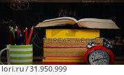 Купить «A table with a pile of books, a cup with pens, and an alarm clock with mathematical equations in the», видеоролик № 31950999, снято 13 июня 2019 г. (c) Wavebreak Media / Фотобанк Лори