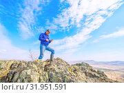 Купить «A handsome mature tourist is standing on the top of a mountain, enjoying climbing and taking selfies.», фото № 31951591, снято 24 апреля 2019 г. (c) Акиньшин Владимир / Фотобанк Лори