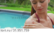 Купить «Woman in bikini applying sunscreen lotion on her body near poolside 4k», видеоролик № 31951759, снято 12 марта 2019 г. (c) Wavebreak Media / Фотобанк Лори