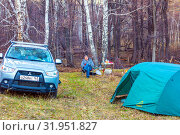 Купить «Russia, South Ural, April 2019: Parking for rest in a birch forest. A tourist sits in a lounge chair near the table with dinner. Auto and tent near.», фото № 31951827, снято 27 апреля 2019 г. (c) Акиньшин Владимир / Фотобанк Лори