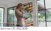 Купить «Woman drinking coffee and using mobile phone in kitchen at comfortable home 4k», видеоролик № 31952839, снято 12 марта 2019 г. (c) Wavebreak Media / Фотобанк Лори