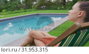 Woman in swimwear relaxing on chair near swimming pool in the backyard 4k. Стоковое видео, агентство Wavebreak Media / Фотобанк Лори