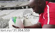 Купить «Male rugby player sitting with rugby ball in stadium 4k», видеоролик № 31954559, снято 9 мая 2019 г. (c) Wavebreak Media / Фотобанк Лори