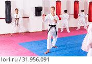 Купить «Preteen boy practicing karate movements with male trainer supervision», фото № 31956091, снято 3 июля 2020 г. (c) Яков Филимонов / Фотобанк Лори