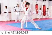 Купить «Preteen boy practicing karate movements with male trainer supervision», фото № 31956095, снято 3 июля 2020 г. (c) Яков Филимонов / Фотобанк Лори
