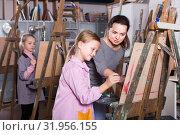 Купить «Positive female teacher assisting student during painting», фото № 31956155, снято 21 августа 2019 г. (c) Яков Филимонов / Фотобанк Лори