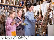 Купить «Skillful woman teacher showing her skills during painting class at art studio», фото № 31956167, снято 21 августа 2019 г. (c) Яков Филимонов / Фотобанк Лори