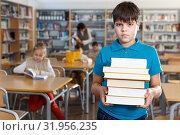 Купить «Upset boy standing with books», фото № 31956235, снято 19 декабря 2018 г. (c) Яков Филимонов / Фотобанк Лори