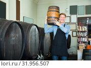 Купить «vigorous man working in winery and holding wine wood in cellar», фото № 31956507, снято 21 сентября 2019 г. (c) Яков Филимонов / Фотобанк Лори