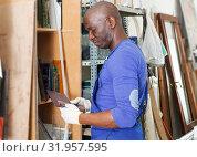 Купить «African-American workman looking at glass samples», фото № 31957595, снято 16 мая 2018 г. (c) Яков Филимонов / Фотобанк Лори