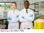 Купить «Experienced male and female scientists standing in laboratory», фото № 31957759, снято 21 марта 2019 г. (c) Яков Филимонов / Фотобанк Лори