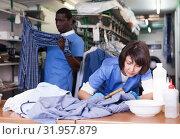 Купить «Female laundry worker during daily work», фото № 31957879, снято 15 января 2019 г. (c) Яков Филимонов / Фотобанк Лори
