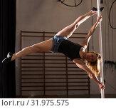 Купить «Young woman in denim shorts practicing pole dancing», фото № 31975575, снято 9 декабря 2019 г. (c) Яков Филимонов / Фотобанк Лори
