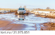 Купить «Russia, Samara, March 2019: A passenger car overcomes a muddy puddle in the spring thaw on a country road.», фото № 31975851, снято 30 марта 2019 г. (c) Акиньшин Владимир / Фотобанк Лори