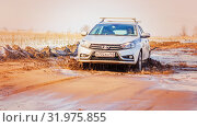 Купить «Russia, Samara, March 2019: A passenger car overcomes a muddy puddle in the spring thaw on a country road.», фото № 31975855, снято 30 марта 2019 г. (c) Акиньшин Владимир / Фотобанк Лори