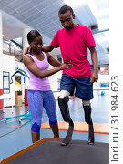 Купить «Female physiotherapist helping disabled man walk with prosthetic leg on ramp in sports center», фото № 31984623, снято 24 марта 2019 г. (c) Wavebreak Media / Фотобанк Лори