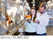 Купить «Smiling family holding bedside lamp in furniture shop», фото № 31985323, снято 29 января 2018 г. (c) Яков Филимонов / Фотобанк Лори