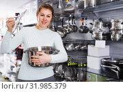 Купить «Young woman is looking modern saucepan in the store», фото № 31985379, снято 5 февраля 2018 г. (c) Яков Филимонов / Фотобанк Лори