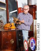 Купить «Positive man carefully examining antiques», фото № 31985443, снято 15 мая 2018 г. (c) Яков Филимонов / Фотобанк Лори
