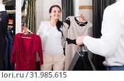Купить «Adult couple purchasing dress and blouse», фото № 31985615, снято 24 октября 2016 г. (c) Яков Филимонов / Фотобанк Лори