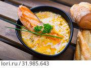 Купить «Delicious cream-soup with salmon and greens, served in bowl with bread at table», фото № 31985643, снято 24 августа 2019 г. (c) Яков Филимонов / Фотобанк Лори