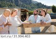 Купить «Friends chatting near wooden fencing», фото № 31994403, снято 11 апреля 2019 г. (c) Яков Филимонов / Фотобанк Лори