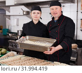 Купить «Two cooks holding baking tray with cannelloni», фото № 31994419, снято 11 апреля 2019 г. (c) Яков Филимонов / Фотобанк Лори