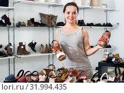 Brunette offers footwear in fashion shoes center. Стоковое фото, фотограф Яков Филимонов / Фотобанк Лори