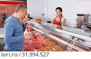 Купить «seller helping attentive customer choosing different sausages», фото № 31994527, снято 22 июня 2018 г. (c) Яков Филимонов / Фотобанк Лори