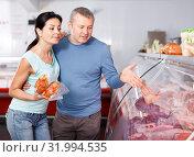 Купить «Positive couple customers choosing meat in shop», фото № 31994535, снято 22 июня 2018 г. (c) Яков Филимонов / Фотобанк Лори