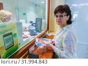 Russia, Samara, June 2019: Sberbank of Russia. Mature woman standing by the window of a savings bank. Text in Russian: Sberbank. Редакционное фото, фотограф Акиньшин Владимир / Фотобанк Лори