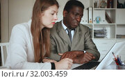 Купить «Young woman and man colleagues working with laptop and papers in office», видеоролик № 32003459, снято 26 апреля 2019 г. (c) Яков Филимонов / Фотобанк Лори