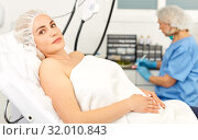 Купить «Young woman waiting for cosmetic procedure in clinic of esthetic cosmetology», фото № 32010843, снято 14 марта 2019 г. (c) Яков Филимонов / Фотобанк Лори