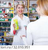 Купить «Seller helping customer to choose care products», фото № 32010951, снято 15 марта 2017 г. (c) Яков Филимонов / Фотобанк Лори