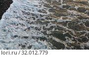Купить «Aerial video of pebble beach natural background. Camera looking down at an angle.», видеоролик № 32012779, снято 14 июля 2019 г. (c) Serg Zastavkin / Фотобанк Лори