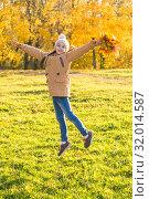 Купить «Счастливая маленькая девочка радуется солнечному осеннему дню, вертикально», фото № 32014587, снято 14 октября 2018 г. (c) Лариса Капусткина / Фотобанк Лори