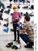 Купить «Man seller assisting boy in trying on roller-skates», фото № 32016375, снято 21 декабря 2016 г. (c) Яков Филимонов / Фотобанк Лори