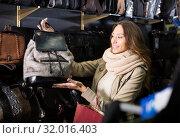 Купить «interested woman buying leather purse in shop», фото № 32016403, снято 9 апреля 2020 г. (c) Яков Филимонов / Фотобанк Лори