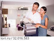 Купить «Couple looking for furnishing materials in store», фото № 32016583, снято 17 июля 2018 г. (c) Яков Филимонов / Фотобанк Лори