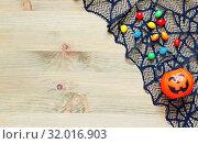 Купить «Halloween background. Spider web, cobweb lace and smiling jack decorations - Halloween tiny bag and candies - as the symbols of Halloween on the wooden background», фото № 32016903, снято 2 октября 2018 г. (c) Зезелина Марина / Фотобанк Лори