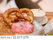 Купить «Focus on pretzel. antique porcelain cup with whipped cream. green chocolate and iced donut», фото № 32017075, снято 9 февраля 2019 г. (c) katalinks / Фотобанк Лори