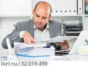 Businessman in shirt viewing documents at the table. Стоковое фото, фотограф Яков Филимонов / Фотобанк Лори
