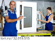 Купить «Workman in blue overalls demonstrating pvc window», фото № 32019515, снято 19 июля 2017 г. (c) Яков Филимонов / Фотобанк Лори