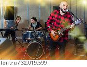 Купить «Guy guitar player and singer practicing with band members in re», фото № 32019599, снято 26 октября 2018 г. (c) Яков Филимонов / Фотобанк Лори