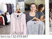Купить «Shop assistant demonstrating jacket on hanger», фото № 32019667, снято 10 октября 2018 г. (c) Яков Филимонов / Фотобанк Лори
