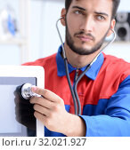 Купить «Young repairman fixing and repairing microwave oven», фото № 32021927, снято 11 июля 2017 г. (c) Elnur / Фотобанк Лори
