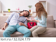 Купить «Young couple in first aid concept at home», фото № 32024179, снято 10 мая 2019 г. (c) Elnur / Фотобанк Лори