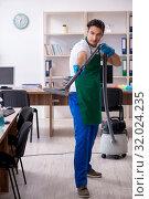 Купить «Young handsome contractor cleaning the office», фото № 32024235, снято 9 мая 2019 г. (c) Elnur / Фотобанк Лори
